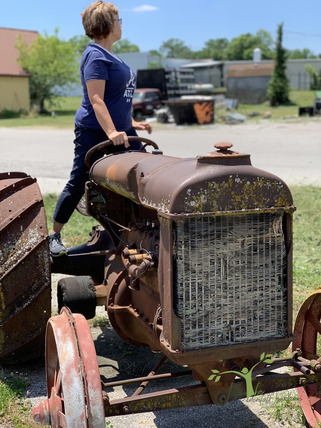 woman on old tractor junking in the ozarks