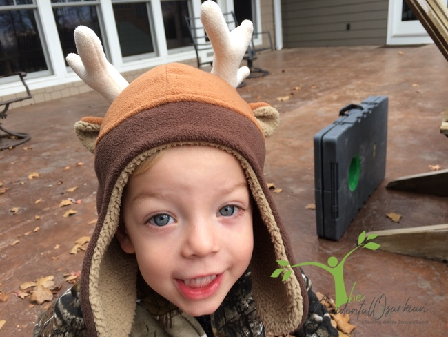 child with deer hat